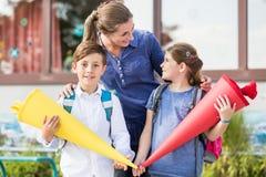 母亲和孩子在第一天有糖果锥体的学校 免版税图库摄影