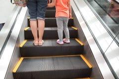 母亲和孩子在自动扶梯 免版税库存照片