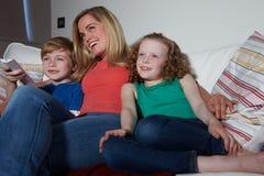 母亲和孩子坐一起看电视的沙发 库存图片