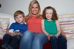 母亲和孩子坐一起看电视的沙发 免版税图库摄影