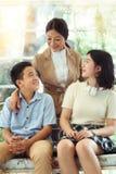 母亲和孩子坐沙发是愉快的 免版税库存图片