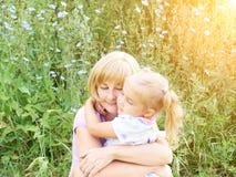母亲和孩子拥抱并且获得室外的乐趣本质上  免版税库存照片
