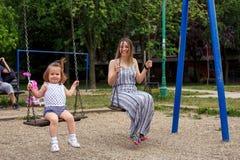 母亲和孩子摇摆的在操场 免版税库存照片