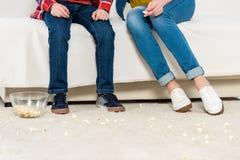 母亲和孩子播种的射击坐长沙发用杂乱溢出的玉米花 免版税库存照片