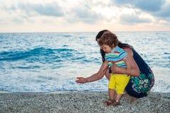 母亲和孩子收集在海滩的小卵石 免版税图库摄影