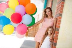 母亲和孩子有五颜六色的气球的 库存照片