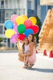 母亲和孩子有五颜六色的气球的 免版税库存照片