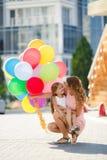 母亲和孩子有五颜六色的气球的 库存图片