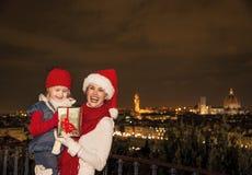母亲和孩子有圣诞节礼物箱子的在佛罗伦萨 库存图片