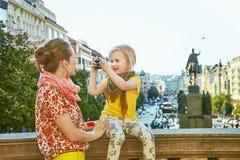 母亲和孩子有拍照片的数字照相机的在布拉格 库存图片
