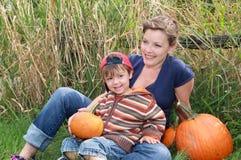 母亲和孩子有的南瓜 免版税图库摄影