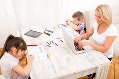 母亲和孩子有膝上型计算机的在家 库存照片