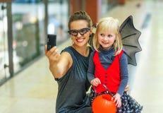 母亲和孩子有采取selfie的数字照相机的 图库摄影