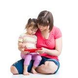 母亲和孩子演奏或读片剂计算机 库存图片