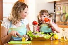 母亲和孩子烹调和获得乐趣在厨房里 库存照片