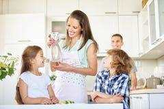 母亲和孩子用玻璃水瓶水 免版税库存图片