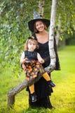 母亲和孩子穿戴了象巫婆,万圣夜 库存图片