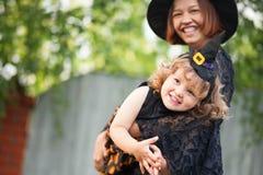 母亲和孩子穿戴了象巫婆,获得乐趣 免版税库存图片