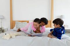 母亲和孩子获得乐趣,当读故事书在卧室时 免版税图库摄影