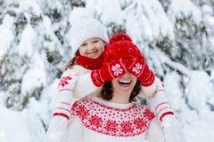 母亲和孩子被编织的冬天帽子的充当雪家庭圣诞节假期 手工制造羊毛帽子和围巾妈妈和孩子的 免版税库存图片