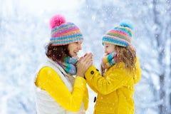 母亲和孩子被编织的冬天帽子的在雪 免版税库存照片