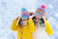 母亲和孩子被编织的冬天帽子的在雪 免版税图库摄影