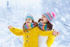 母亲和孩子被编织的冬天帽子的在雪 免版税库存图片