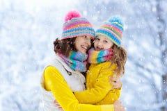 母亲和孩子被编织的冬天帽子的在雪 库存照片