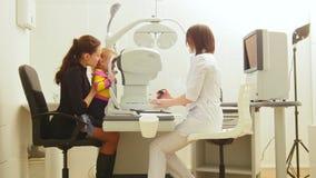 母亲和孩子诊所的检查小孩` s视觉的眼科医生` s室验光师的 影视素材