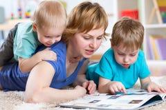 母亲和孩子阅读书在家 图库摄影