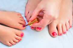 母亲和孩子绘他们的与指甲油的脚 库存图片