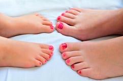 母亲和孩子绘他们的与指甲油的脚 库存照片