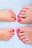 母亲和孩子绘他们的与指甲油的脚 免版税库存图片