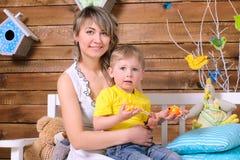 母亲和小儿子坐长凳户内 免版税库存照片