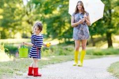 母亲和小可爱的孩子女孩女儿雨靴的 免版税图库摄影