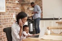 母亲和小女儿作为父亲的用途膝上型计算机准备膳食 免版税库存图片