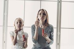 母亲和小女儿吹的肥皂泡 库存照片