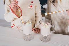 母亲和小女儿喝可可粉用蛋白软糖 库存照片