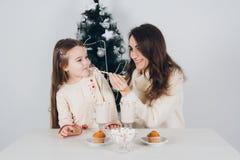 母亲和小女儿喝可可粉用蛋白软糖 图库摄影