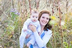 年轻母亲和小女儿在公园 免版税库存图片