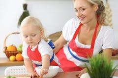 母亲和小女儿在厨房里烹调 一起花费时间全部或愉快的家庭观念 库存图片