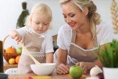 母亲和小女儿在厨房里烹调 一起花费时间全部或愉快的家庭观念 免版税库存照片