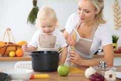 母亲和小女儿在厨房里烹调 一起花费时间全部或愉快的家庭观念 免版税图库摄影