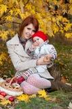母亲和小女儿在秋天公园 免版税库存照片