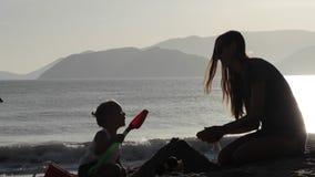 母亲和小女儿大厦沙子剪影在海滩防御 影视素材