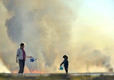 母亲和小女儿熄灭从喷壶的火 免版税图库摄影