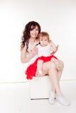 母亲和小女儿红色裙子的 免版税库存照片