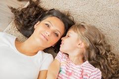 母亲和小女儿耳语在母亲的耳朵 免版税库存图片