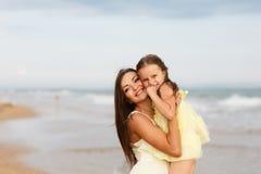 母亲和小女儿获得在海滩的乐趣 免版税图库摄影