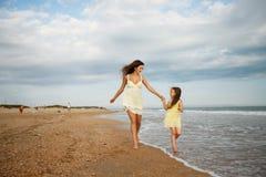 母亲和小女儿获得在海滩的乐趣 免版税库存图片